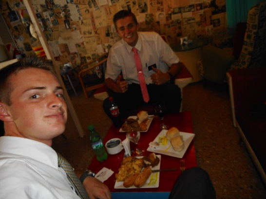 Elders Mathias and Cannon eating lunch at a member's restaurant